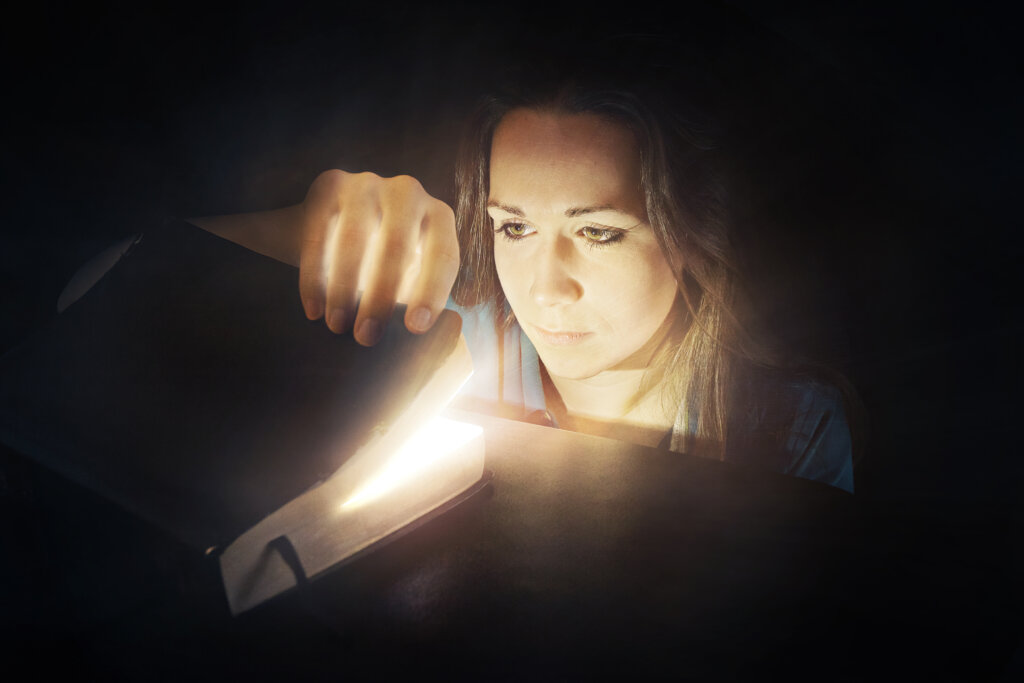 a woman looks inside a bible that is glowing rXXk11feA 1024x683 - We have Heard HIm Ourselves