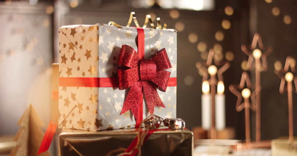 storyblocks beautifully wrapped christmas presents on the background of stylish decorations and lights in warm golden and red tones HnJgH10Ab scaled 1024x540 -